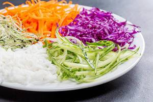 Sliced fresh vegetables and rice on a plate closeup