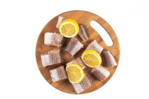 Sliced Hake Fish on the wooden board with Lemon
