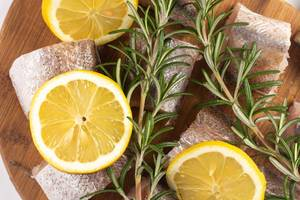 Sliced Hake Fish on the wooden board with Rosemary branches and Lemon