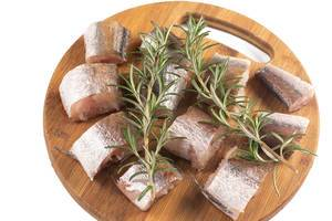 Sliced Hake Fish on the wooden board with Rosemary branches