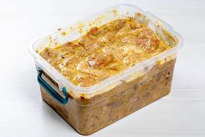 Sliced meat marinated with spices in a plastic container for barbecue