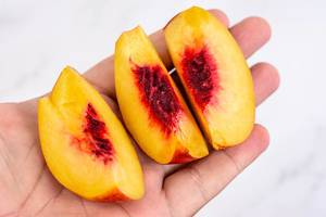 Sliced Peach in the hand above white background