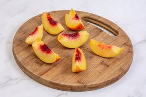Sliced Peach on the round wooden board