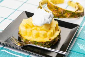 Sliced Pineapple on the plate with pouring cream