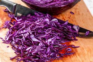 Sliced purple cabbage on kitchen Board