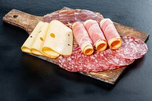 Sliced salami, ham, and cheese on an old kitchen wooden Board on a black background (Flip 2019)