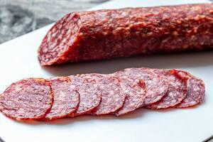 Sliced salami on a white kitchen Board