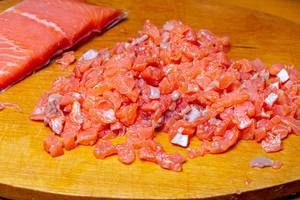 Sliced salmon fillet on a wooden kitchen Board