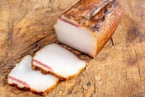 Sliced smoked lard on a wooden background