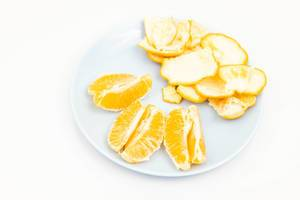 Sliced Tangerine served on the blue plate above white background