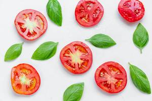 Sliced tomato and fresh Basil leaves on white background