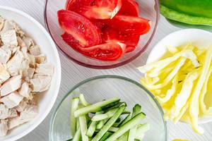 Sliced tomatoes, cucumbers, peppers and chicken fillet in glass bowls (Flip 2019)