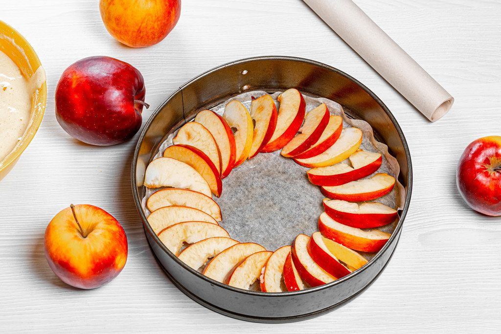 Slices of apples laid out on parchment paper in a baking sheet