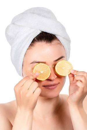 Slices of lemon in the hands of a girl in front of her eyes