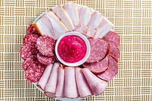 Slicing of ham and different varieties of sausage on a plate with sauce
