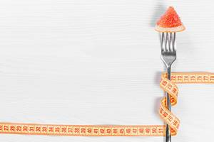 Slimming concept-a piece of grapefruit on a fork wrapped with measuring tape on a white wooden background