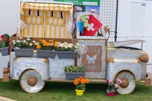 Small van made of sheet with flower pots. Garden decoration