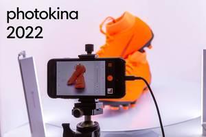 """Smartphone auf einem Stativ, mit geöffneter Fotoapparat für Produktfotografie und dem Bildtitel """"photokina 2022"""""""