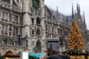 Smartphone fotografiert Kölner Dom mit Weihnachtsmarkt und Weihnachtsbaum