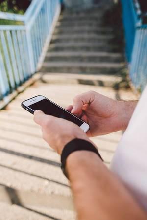 Smartphone in den Händen eines jungen Mannes