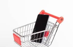 Smartphone liegt in Einkaufswagen vor weißem Hintergrund