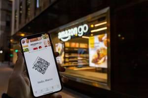 Smartphone mit Amazon-Go App vor einem Ladengeschäft von Amazon Go in Chicago
