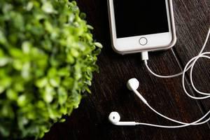 Smartphone mit angeschlossenen Kopfhörern auf einem braunen Holztisch, aus der Vogelperspektive