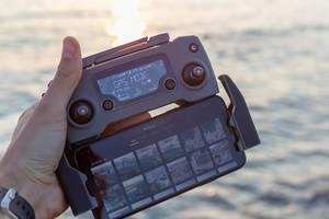 Smartphone mit der DJI Mavic 2 Drohnensteuerung im GPS Mode, vor dem Mittelmeer in Griechenland