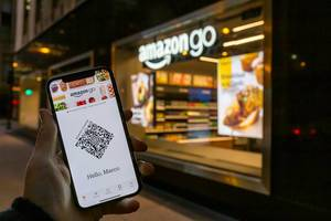 Smartphone with Amazon Go app in front of an Amazon Go store in Chicago