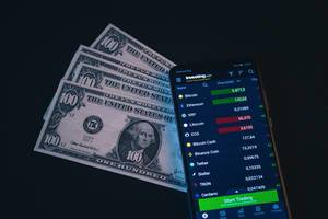 Smartphone zeigt Wert von Kryptowährungen neben amerikanischen Geldscheinen, vor schwarzem Hintergrund