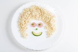 Smiling face made of macaroni, sausage, avocado slice and green peas