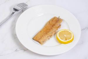 Smoked Mackerel fish with Lemon on the white plate