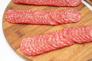 Smoked red Sausage sliced and arranged on the wooden board