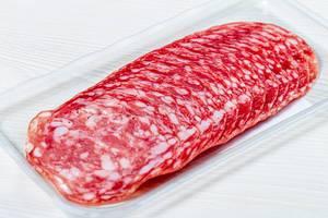 Smoked salami sausages slices on white background (Flip 2019)
