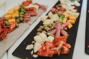 Snacks auf einem Hochzeit: Oliven, Schinken, Käse, Würstchen und getrocknete Tomaten auf schwarzem Brett