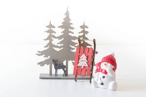Snowman with sleighs in the forest