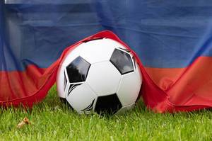 Soccer ball and Russian flag on the green gras