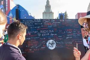 Soccer fans writing messages on black board at fan fest