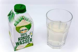 Solevita 100% Kokoswasser im Tetrapack neben einem gefüllten Glas