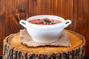Soljanka- Suppe, aus der osteuropäischen Küche, in einer weißen Terrine und auf einem Baumstumpf serviert