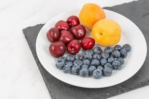 Sommerliches Obst wie Blaubeeren, Kirschen und Aprikosen, werden auf einem Teller mit einer Schiefersteinplatte serviert