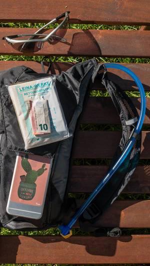 Sonnenbrille, Camelbak Trinkrucksack, Rettungsdecke, Handy und Bargeld