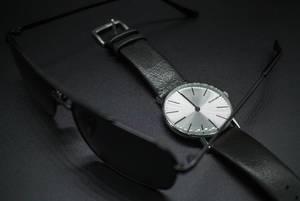 Sonnenbrille und Armbanduhr mit schwarzem Lederband. Accessoires passend zu formeller Kleidung
