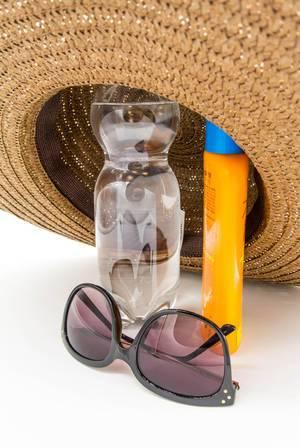 Sonnenbrille, Wasserflasche und Sonnenkreme unter einem Strohhut