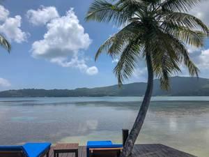 """Sonnenliegen auf Holzsteg unter Palmen des """"Iles des Palmes"""" Resort mit Blick über Baie Ste. Anne von Praslin, Seychellen"""