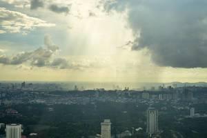 Sonnenstrahlen dringen durch die Wolken über Kuala Lumpur