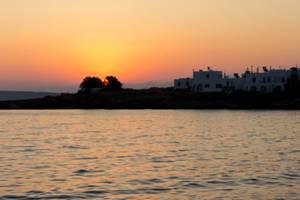Sonnenuntergang mit rotem Himmel über der griechischen Hafenstadt Naoussa auf Paros & dem Mittelmeer im Vordergrund