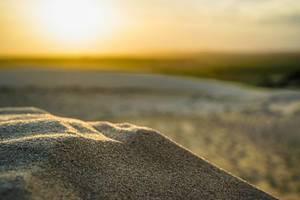 Sonnenuntergang spiegelt sich in den Sandkörnern der weißen Dünen in Mui Ne, Südvietnam