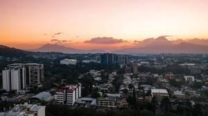 Sonnenuntergang über dem Gebäuden von Guatemala City und den dahinter liegenden Vulkanen
