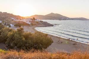Sonnenuntergang über Paros taucht Strand und typische griechische Bauten in goldenes Licht